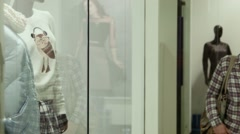 The girl looks at a show-window of clothing store in mall Stock Footage