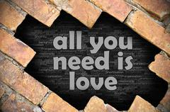 Hole in the brick wall with word all you need is love Stock Photos