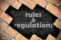 Hole in the brick wall with word rules & regulations - stock photo