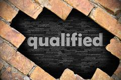 Hole in the brick wall with word qualified Stock Photos