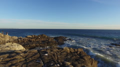 The sun sets on the rock formations on the ocean Stock Footage