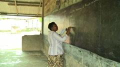 ADEISO CLASSROOM TEACHER WRITES ON BLACKBOARD PAN TO STUDENTS Stock Footage