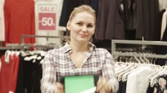 Stock Video Footage of The seller shows the tablet with the green screen in mall