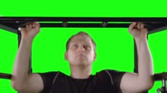MCU Man Doing Pull Ups on Exercise Frame with Green Background 4K Stock Footage