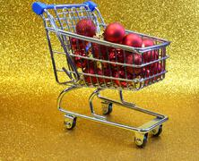 Stock Photo of shopping cart withred decorative Christmas balls and golden glitter backgroun