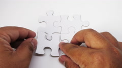 Hand completing White Jigsaw Puzzle with steps 1 to 4 written on it. Stock Footage