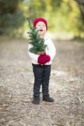 Baby Girl In Red Mittens and Cap Holding Small Christmas Tree Outdoors. - stock photo
