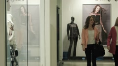 Two girls look at a show-window of shop - stock footage
