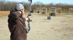 4K young  man shooting a compound bow at target - stock footage