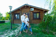 Happy young family near the wooden house Stock Photos