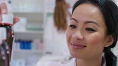 4K Worker in a pharmacy checking stock & putting bottles on shelves Stock Footage