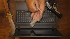 Crook thieve spy hacker criminal terrorist gun in laptop putting on gloves - stock footage
