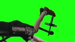 CU Man Doing Leg Curls on Exercise Bench with Green Background 4K - stock footage