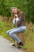 Sad beautiful young woman sitting on road suitcase Stock Photos