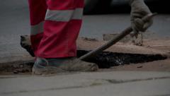 Man uses metal rod on ruptured asphalt. - stock footage