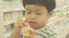Asian boy eating ice cream in supermarket, retro video hd, Stock Footage