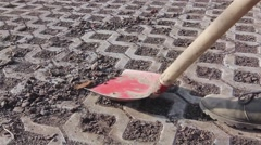 Dirt stripping, scraping with red shovel, cleaning urban ground. - stock footage