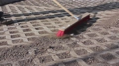 Worker is cleaning new parking place with red broom. Stock Footage
