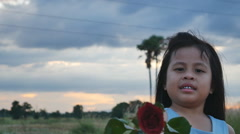 Red roses In hand girl on field and sky background, Stock Footage