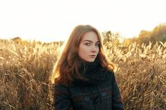 Young beautiful redhead woman faded meadow cold season outdoors - stock photo