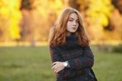 Young beautiful redhead woman autumn foliage cold season outdoors - stock photo