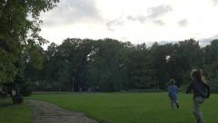 Adults walking and children running in Herastrau Park in Bucharest Stock Footage
