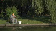 One man fishing on the waterfront in Herăstrău Park, Bucharest Stock Footage