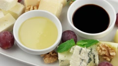 Different types of cheese on a white long plate Stock Footage