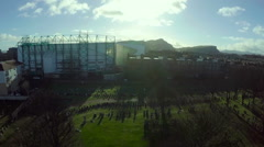 Aerial shot of Easter Road stadium in Edinburgh with Arthurs seat and the Crags Stock Footage
