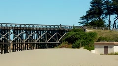 Pan of bridge over a creek by the beach with walkers on bridge Stock Footage