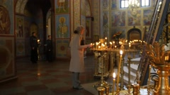 Woman in Saint Michael's Male Monastery Christmas Eve Kiev Woman Burns a Candle - stock footage