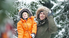 Attractive family of three having fun in a snow winter park Stock Footage