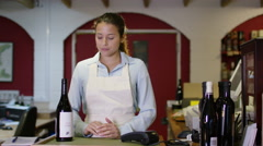 4K Portrait of friendly shopkeeper standing behind counter in wine shop Stock Footage