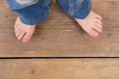 Top view of jeans and feet from a little girl - stock photo
