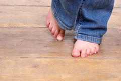 Low angle of little girl with bare feet - stock photo