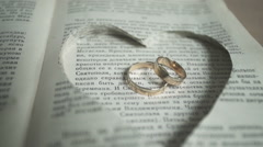 Wedding rings on a book page. Stock Footage