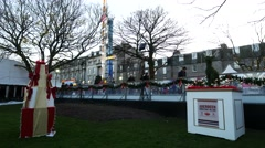 Many adults and children play ice skate at Aberdeen Christmas Village Stock Footage