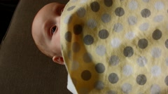 Close up of A Caucasian Baby Playing Peek-A-Boo with a sheet in His Bedroom Stock Footage