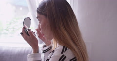 Handheld shot of beautiful latina woman doing make up in mirror Stock Footage