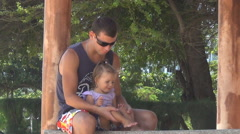 Dad and baby playing in the gazebo. girl stomping feet.They are laughing. Arkistovideo