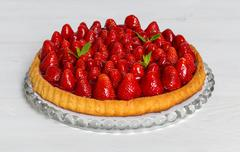 Strawberry cake with mint on white wood - stock photo