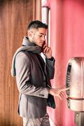 Handsome stylish young man using a pay phone - stock photo
