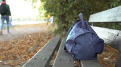 Suspicious bag laying on park bench with no one around 4k Stock Footage