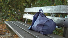 Bag left behind laying on park bench in city center 4k Stock Footage