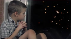 Boy waiting for the miracle of the window late at night - stock footage