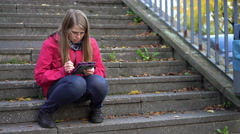 Female sitting on steps outdoors reading ebook 4k - stock footage