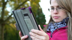 Female outdoors at park reading a book on the tablet 4k Stock Footage