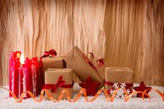 Christmas gifts and red Advent candle. Stock Photos