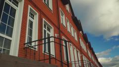 Clouds floating above row of red brick townhouses - stock footage
