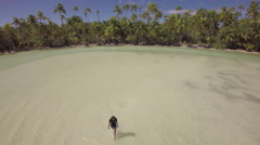 Aerial view of a girl walking in a tropical lagoon - Tetiaroa, French Polynesia - stock footage